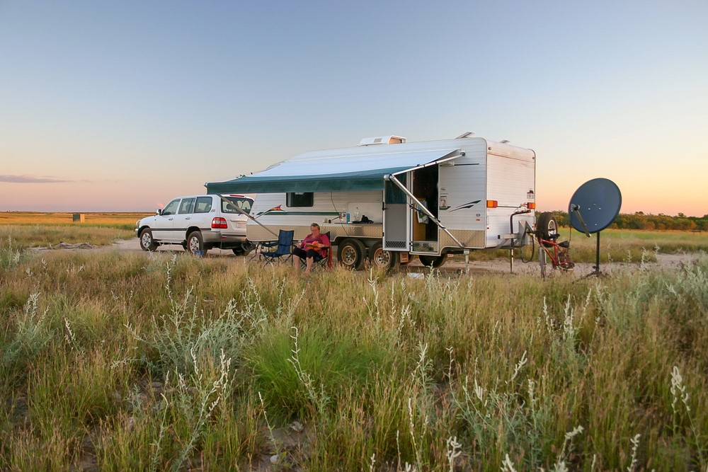 Grey nomads sit beside their caravan in the Australian landscape
