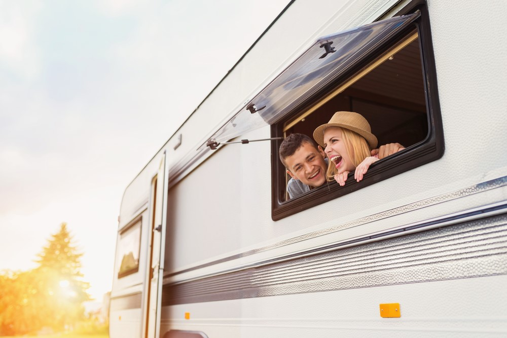 Young couple laughing in a white caravan