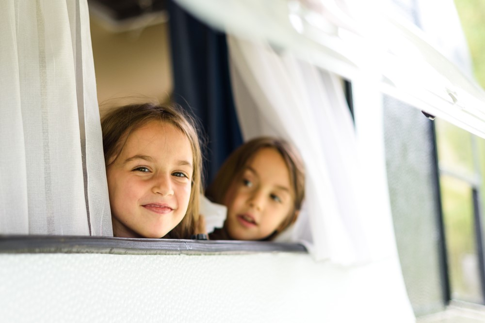 Two girls look out of a white caravan window with curtains