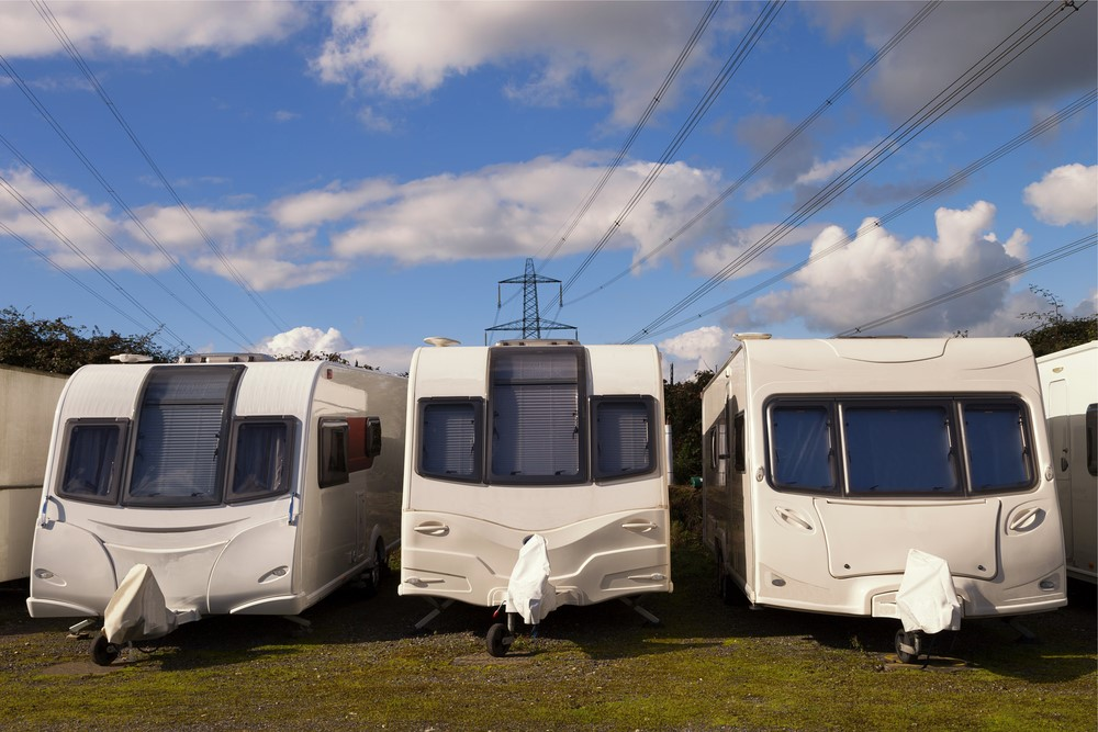 Three Caravans in a row on a sunny day with clouds in the sky with electricity cables in the background