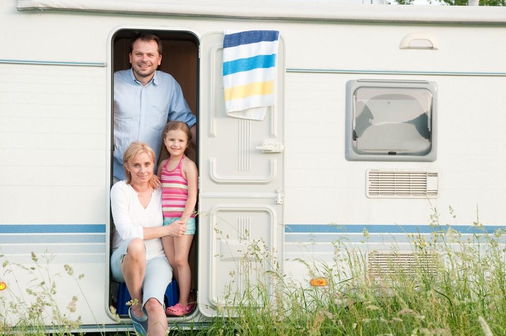 Family smiling in the doorway of a caravan