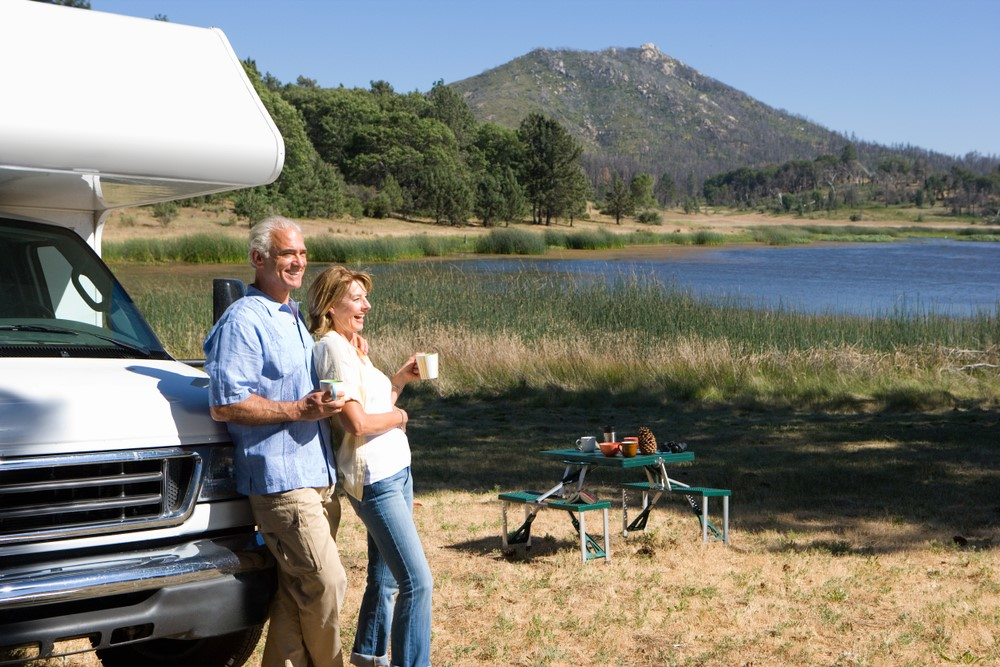 Retired couple relaxing by their caravan on the edge of a lake