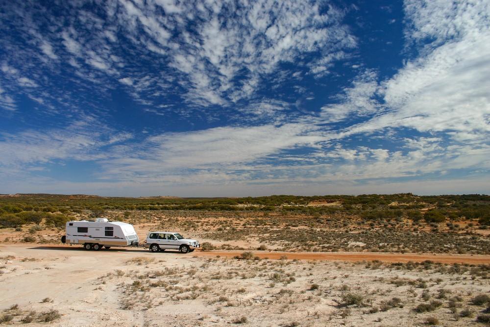 White four wheel drive and caravan going through Australian outback